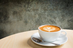 ein Tasse Kaffee und ein Hintergrund der Betonmauerbeschaffenheit mit Spindel Lizenzfreies Stockfoto