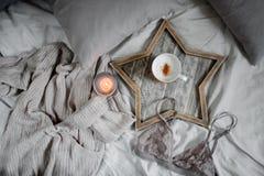Ein Tasse Kaffee und eine Kerze in einem skandinavischen hölzernen Behälter in einem gemütlichen Bett mit Kissen lizenzfreies stockfoto