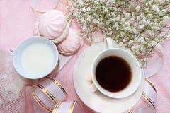 Ein Tasse Kaffee und eine Schale Milch auf der Morgentabelle, dem Nachtisch und den Frühlingsblumen lizenzfreie stockfotos