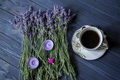 Ein Tasse Kaffee und Lavendelblumen auf einem dunkelblauen hölzernen Hintergrund stockfotos