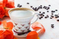 Ein Tasse Kaffee und Rosen auf einem Holztisch Stockfotos