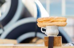 Ein Tasse Kaffee und ein süßes Brötchen an dem Arbeitsplatz stockbilder