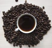 Ein Tasse Kaffee unter den Körnern des Kaffees Stockfotografie