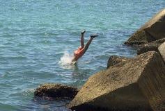 Ein Tauchen in das Meer eines tapferen Jungen Stockbild