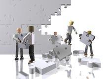 Ein Team, das zusammenarbeitet, um ein Puzzlespiel aufzubauen Lizenzfreies Stockfoto
