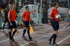 Ein Team des Fußballs fungiert heraus auf dem Feld vor dem Match als Schiedsrichter Stockfotografie