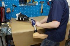 Ein Techniker justiert einen prothetischen Fuß. Stockbild
