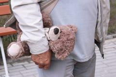 Ein Teddybär in der Hand eines Mannes Weg der alten Person auf der Straße Großvater hält ein Spielzeug eines Enkel oder Enkelin ` Lizenzfreies Stockfoto