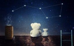 Ein Teddybär mit einem kleinen Bären sitzt an der Nacht auf dem Dach des Hauses und an den Blicken an der Konstellation des Big B lizenzfreies stockbild