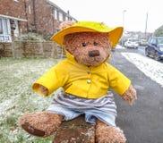 Ein Teddybär sitzt auf einer Wand draußen im Schnee, der einen gelben Regenmantel und einen Hut trägt Stockbild