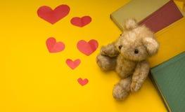 Ein Teddybär sitzt nahe Büchern auf einem gelben Hintergrund von zerstreuten Herzen stockfoto
