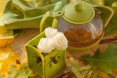 Ein Teetopf, eine Schale Kräutertee, Blumen und Herbstlaub Lizenzfreies Stockfoto