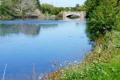 Ein Teich mit einer Bogenbrücke Stockfotos