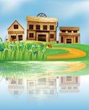 Ein Teich mit einer Reflexion der Holzhäuser stock abbildung
