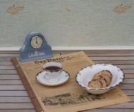 Ein Teil eines englischen Teesatzes vor einer hellblauen Wedgwood-Uhr, Jasperware, auf einem alten deutschen Tageszeitung Der-Pat lizenzfreie stockbilder