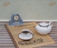 Ein Teil eines englischen Teesatzes vor einer hellblauen Wedgwood-Uhr, Jasperware, auf einem alten deutschen Tageszeitung Der-Pat stockfotos