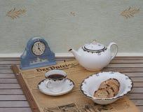 Ein Teil eines englischen Teesatzes vor einer hellblauen Wedgwood-Uhr, Jasperware, auf einem alten deutschen Tageszeitung Der-Pat stockfoto