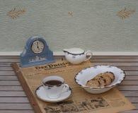 Ein Teil eines englischen Teesatzes vor einer hellblauen Wedgwood-Uhr, Jasperware, auf einem alten deutschen Tageszeitung Der-Pat stockbilder
