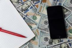 Ein Telefon, ein Notizbuch und eine Stiftlage auf zerstreut hundert Dollarscheinen stockfotografie