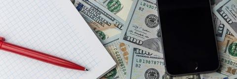 Ein Telefon, ein Notizbuch und eine Stiftlage auf zerstreuten Dollarscheinen lizenzfreie stockfotografie