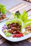 Ein Teller der thailändischen Art gor Wurst mit Seitenkräutern, Paprika, Kalk, Ingwer, Acajounuss Knoblauch und Schalotte auf Spe Stockbilder