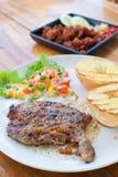 Ein Teller des Rindfleischsteaks mit Karottenbohnenmais und -brokkoli auf Holz Lizenzfreie Stockbilder
