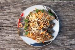 Ein Teller von gebratenen Fischen auf dem Hintergrund des alten Holztischs Stockfotos