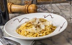 Ein Teller von Spaghettis carbonara diente auf einer Marmortabelle mit Wein Lizenzfreies Stockfoto