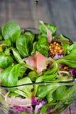 Ein Teller von verschiedenen Arten von bunten Kopfsalatblättern, von Arugula, von Prosciuttoschinken, von Olivenöl und von Dijon- Stockbild