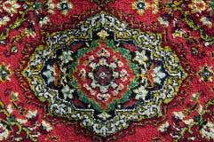 Ein Teppich wird durch ein dekoratives Volksmuster verziert Stockbilder