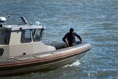 Ein Terrorist oder ein Saboteur in einem dunklen Anzug auf einem kleinen Boot lizenzfreie stockfotos