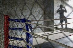 Ein thailändischer Boxring, während thailändischer Boxer kommt, Muay thailändisches zu kämpfen, kann durch seinen Schatten sehen Lizenzfreies Stockfoto