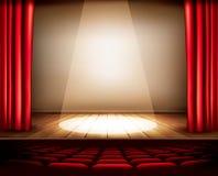 Ein Theaterstadium mit einem roten Vorhang, Sitzen und einem Scheinwerfer Stockfoto