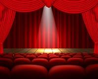 Ein Theaterstadium mit einem roten Vorhang, Sitzen und einem Scheinwerfer Lizenzfreie Stockfotos
