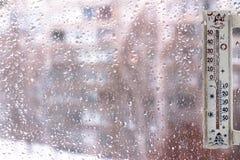 Ein Thermometer auf den Fenstern bedeckt mit Regentropfen, als Symbol des schlechten Wetters Lizenzfreie Stockfotos