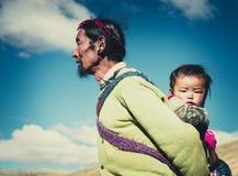 Ein tibetanischer Landwirt mit seinem Kind lizenzfreies stockfoto