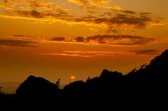 Ein tiefer orange Sonnenuntergang silhouettiert die Felsen an den Hinterwellen stockbilder