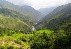 Ein tiefes Tal in Neapal mit den Bergspitzen bedeckt mit Wolken Stockbild