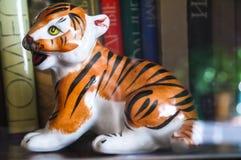 Ein Tigerjunges Dekorative Porzellanfigürchen der Weinlese auf dem Bücherregal Stockfoto