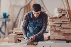 Ein Tischler arbeitet an Holzbearbeitung die Werkzeugmaschine Tischler, der an Holzbearbeitungsmaschinen im Zimmereishop arbeitet lizenzfreie stockbilder