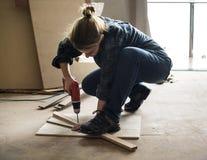 Ein Tischler, der ein Bohrgerät auf einem Holz verwendet Stockfoto
