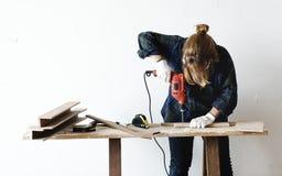 Ein Tischler, der ein Bohrgerät auf einem Holz verwendet Lizenzfreie Stockfotografie