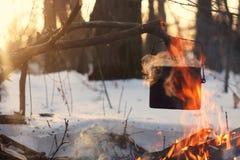 Ein Topf im Feuer, Wasser wird im Winterwald erhitzt Stockfotos
