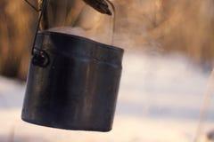 Ein Topf im Feuer, Wasser wird im Winterwald erhitzt Lizenzfreies Stockbild