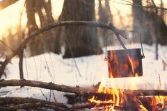 Ein Topf im Feuer, Wasser wird im Winterwald erhitzt Lizenzfreie Stockbilder