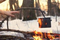 Ein Topf im Feuer, Wasser wird im Winterwald erhitzt Stockfotografie