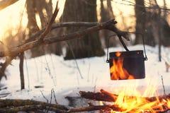 Ein Topf im Feuer, Wasser wird im Winterwald erhitzt Stockbilder