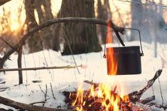Ein Topf im Feuer, Wasser wird im Winterwald erhitzt Lizenzfreie Stockfotos