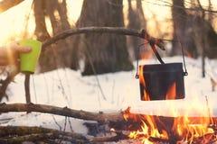 Ein Topf im Feuer, Wasser wird im Winterwald erhitzt Stockfoto