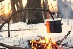 Ein Topf im Feuer, Wasser wird im Winterwald erhitzt Stockbild